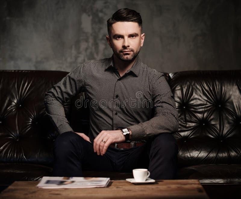 Säker stilig skäggig man med kopp kaffesammanträde på den bekväma lädersoffan på mörk bakgrund royaltyfria bilder