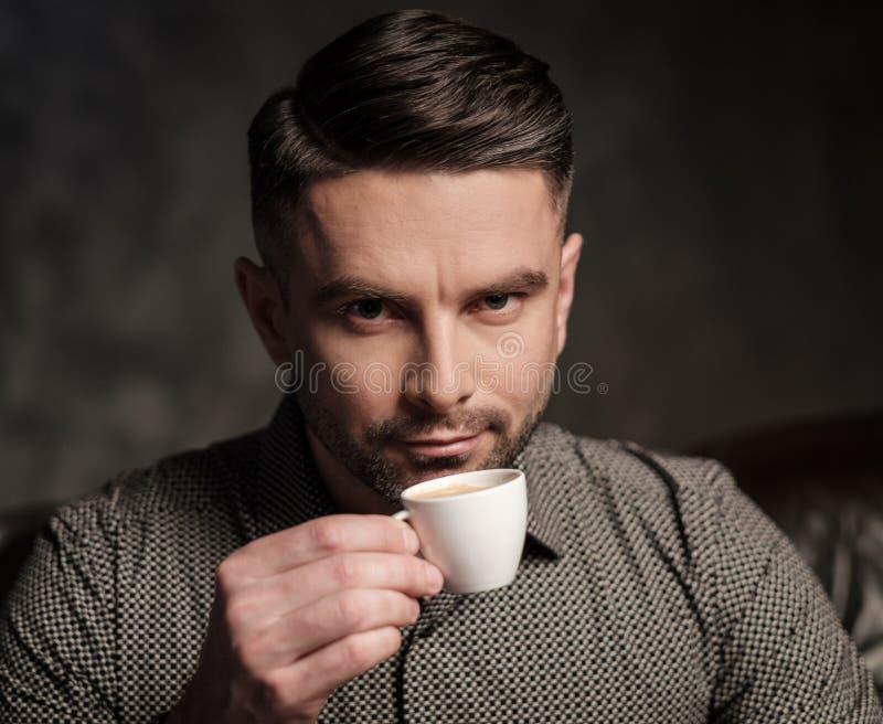 Säker stilig skäggig man med kopp kaffesammanträde på den bekväma lädersoffan på mörk bakgrund royaltyfri bild