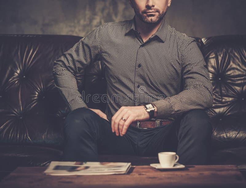 Säker stilig skäggig man med kopp kaffesammanträde på den bekväma lädersoffan på mörk bakgrund arkivfoton