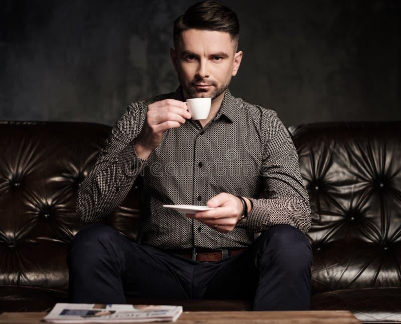 Säker stilig skäggig man med kopp kaffesammanträde på den bekväma lädersoffan på mörk bakgrund arkivfoto