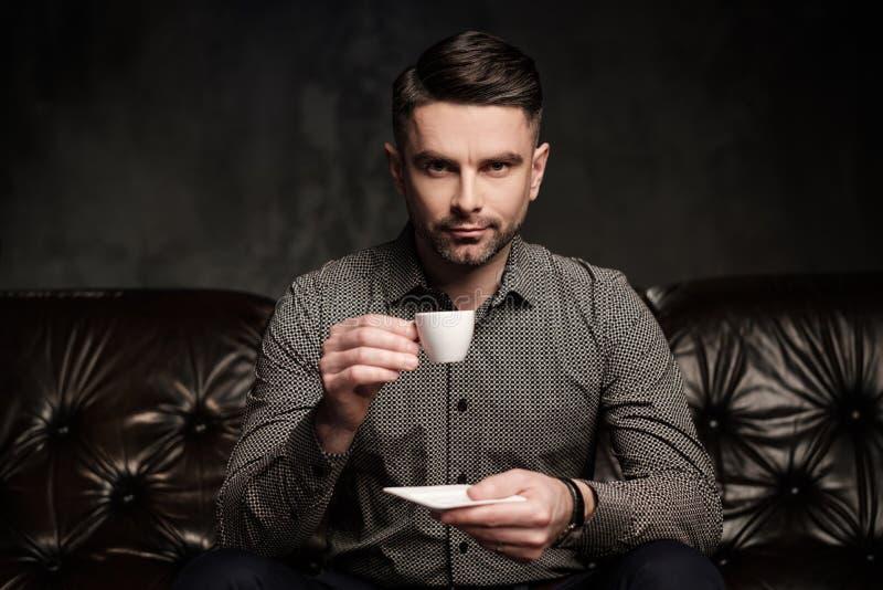 Säker stilig skäggig man med kopp kaffesammanträde på den bekväma lädersoffan på mörk bakgrund royaltyfri fotografi