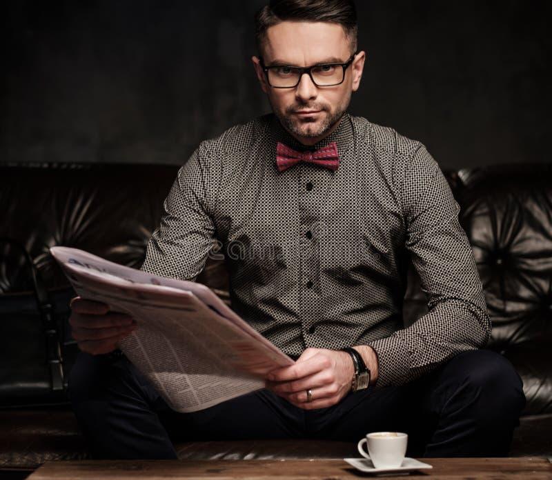 Säker stilig skäggig man med kopp kaffesammanträde på den bekväma lädersoffan på mörk bakgrund arkivbild