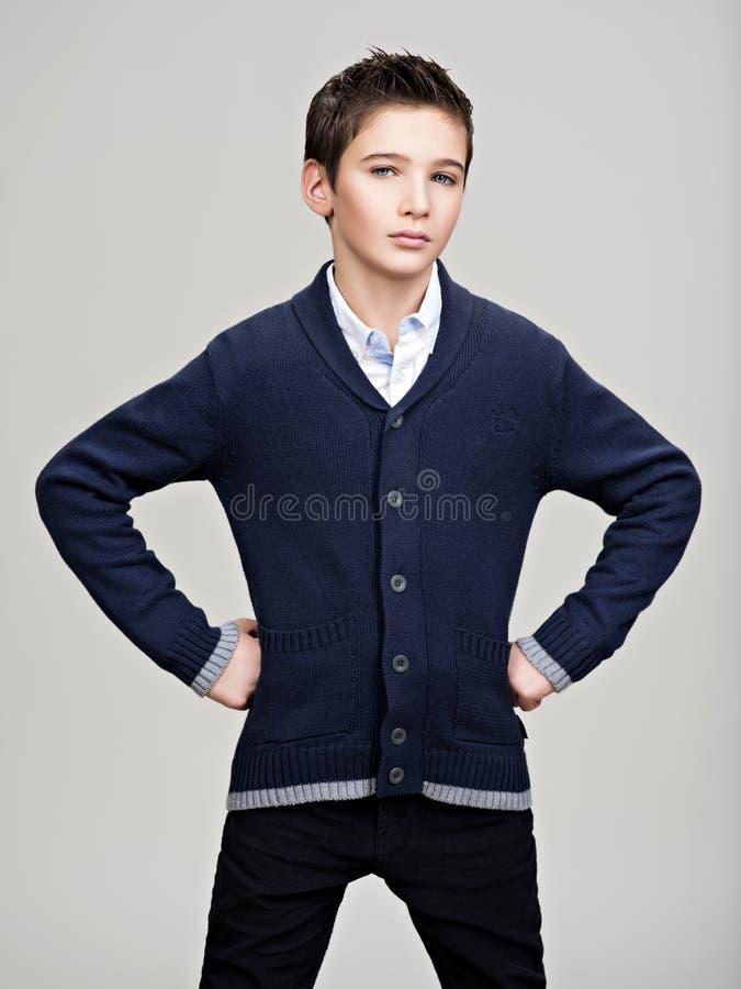 Säker tonårs- pojke som poserar på studion royaltyfri bild