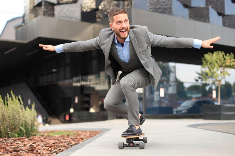 Säker ung affärsman i affärsdräkt på longboarden som skynda sig till hans kontor, på gatan i staden arkivbild