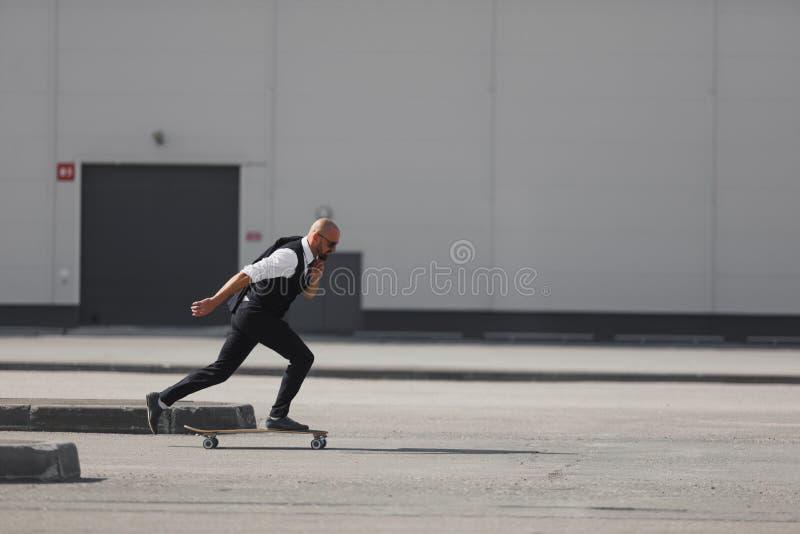 Säker ung affärsman i affärsdräkt på longboarden som skynda sig till hans kontor, på gatan i staden royaltyfri fotografi