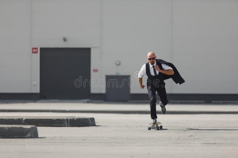 Säker ung affärsman i affärsdräkt på longboarden som skynda sig till hans kontor, på gatan i staden royaltyfria bilder