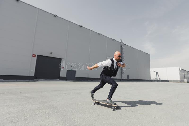 Säker ung affärsman i affärsdräkt på longboarden som skynda sig till hans kontor, på gatan i staden royaltyfria foton