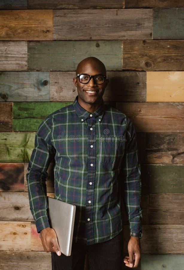 Säker ung affärsman som ler mot träväggen royaltyfria foton