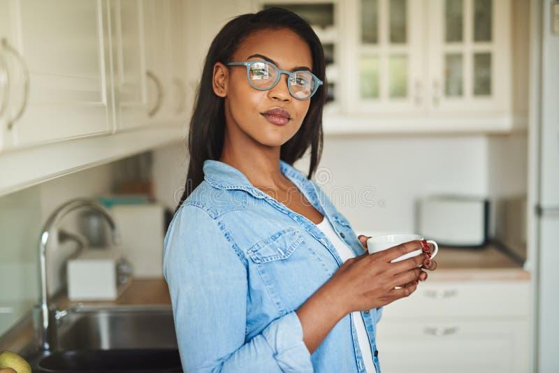 Säker ung afrikansk kvinna som dricker ett kaffe i hennes kök arkivbilder