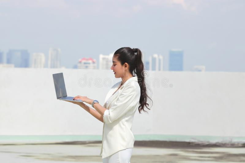 Säker ung asiatisk bärbar dator för innehav för affärskvinna med händer Internet- och teknologibegrepp royaltyfria foton