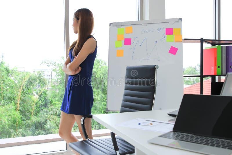 Säker ung asiatisk utövande kvinna som i regeringsställning ser till och med fönster Fundersam och ledarskapaffärsidé arkivfoto