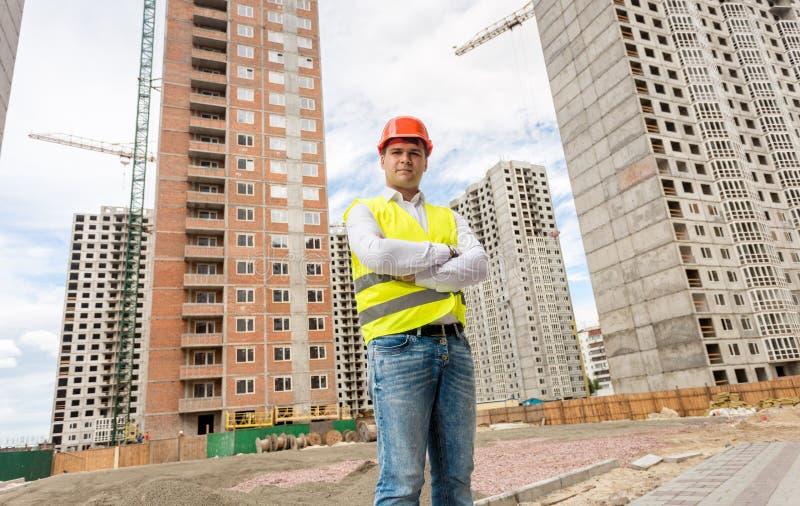Säker ung konstruktionstekniker som poserar mot byggnadsplats arkivbild