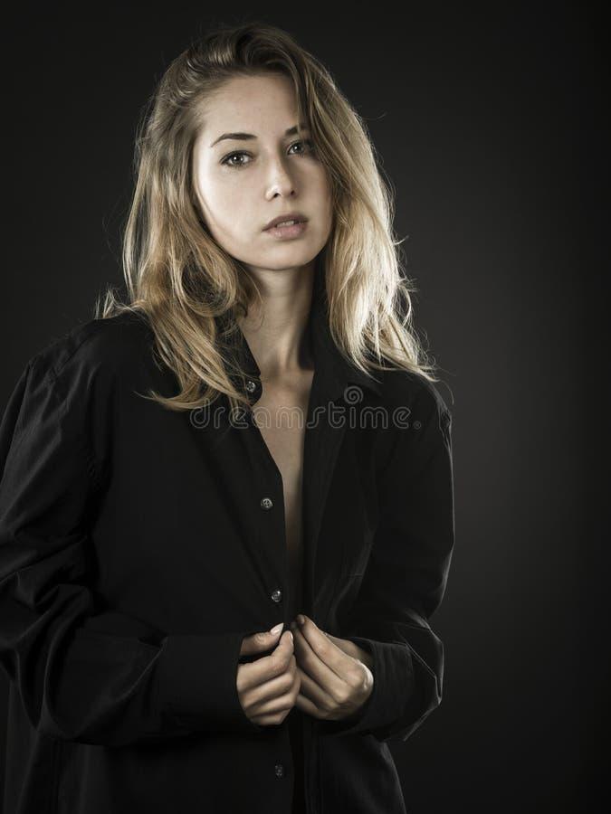 Säker ung kvinna med den knäppte upp skjortan fotografering för bildbyråer