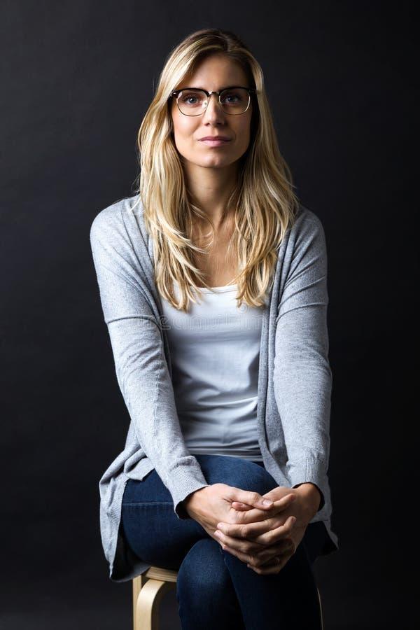 Säker ung kvinna med glasögon som ser kameran över svart bakgrund arkivbilder