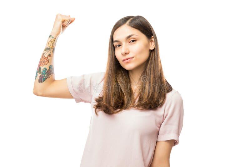 Säker ung kvinna som böjer hennes biceps royaltyfri bild