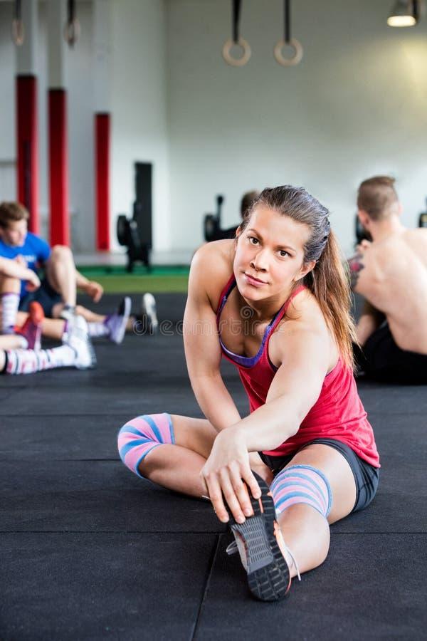 Säker ung kvinna som gör sträcka övning arkivfoton
