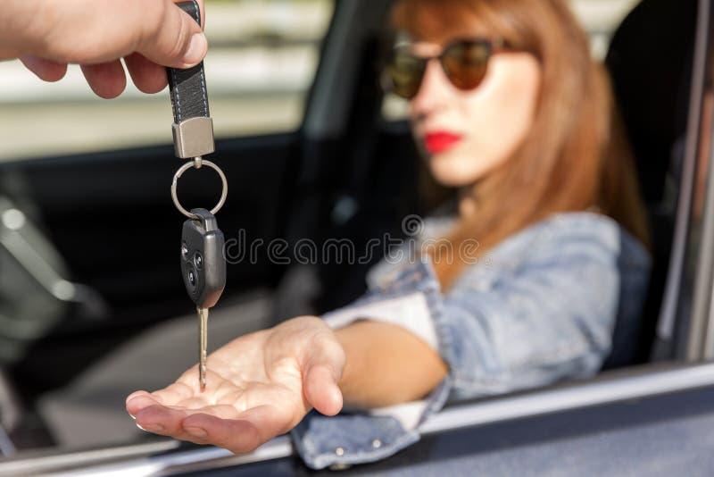 Säker ung kvinna som mottar tangenterna av bilen royaltyfri fotografi