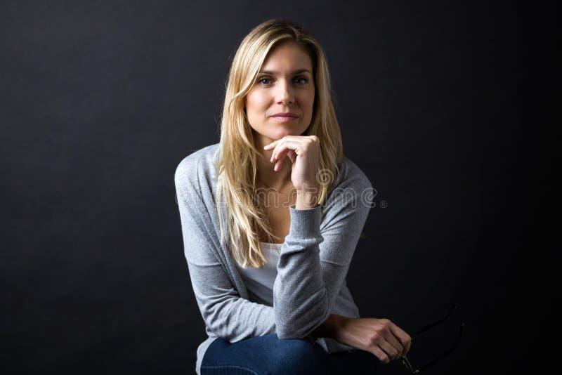 Säker ung kvinna som ser kameran över svart bakgrund royaltyfri bild