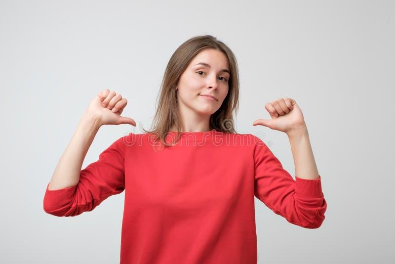 Säker ung nätt kvinna som är stolt och och att peka fingrar, exempel för att följa arkivfoton