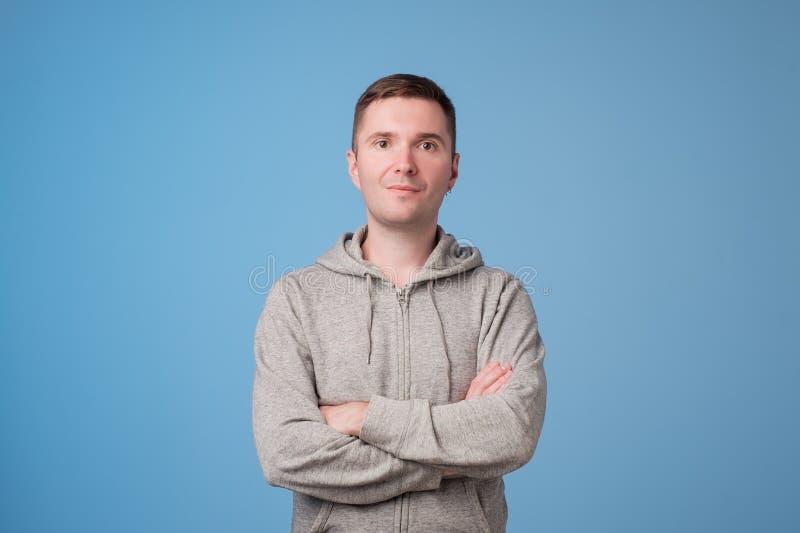 Säker ung stilig man som håller armar korsade och ler, medan stå mot blå vit bakgrund royaltyfria foton