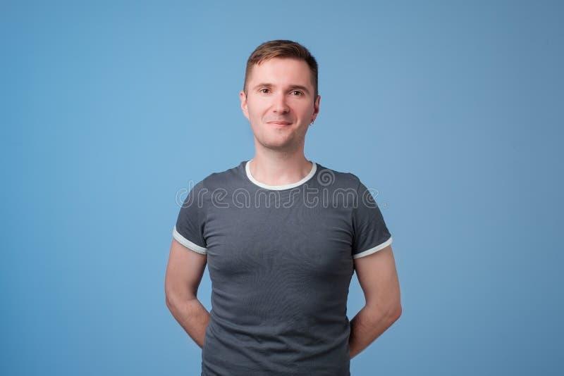 Säker ung stilig man som håller armar korsade och ler, medan stå mot blå vit bakgrund arkivbilder