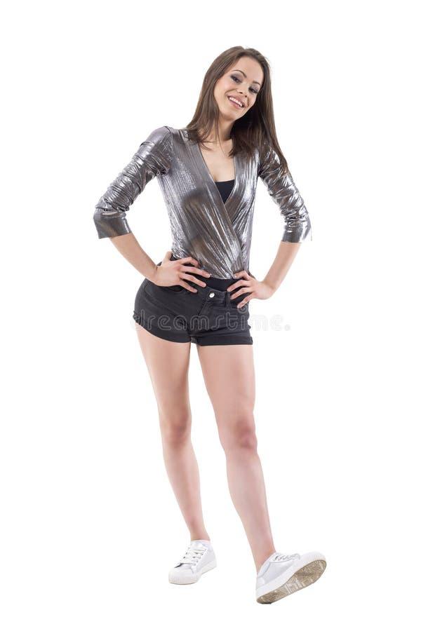 Säker ung ursnygg kvinnlig modemodell som poserar i skinande metallisk skjorta och moderna silvergymnastikskor royaltyfri foto