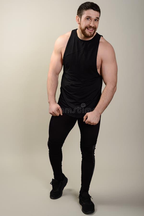 Säker villig ung idrotts- man i sportswearen som ser kameran Full stående för kropplängd över vit studiobakgrund royaltyfri bild