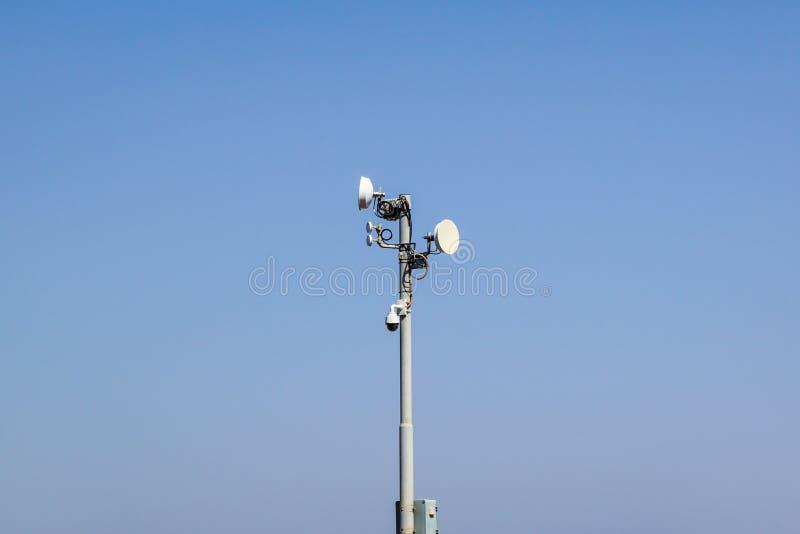 Säkerhet och satellitsystem med en bevakningkamera, en antenn och en kommunikationsdisk på en pol mot ett soligt royaltyfria bilder