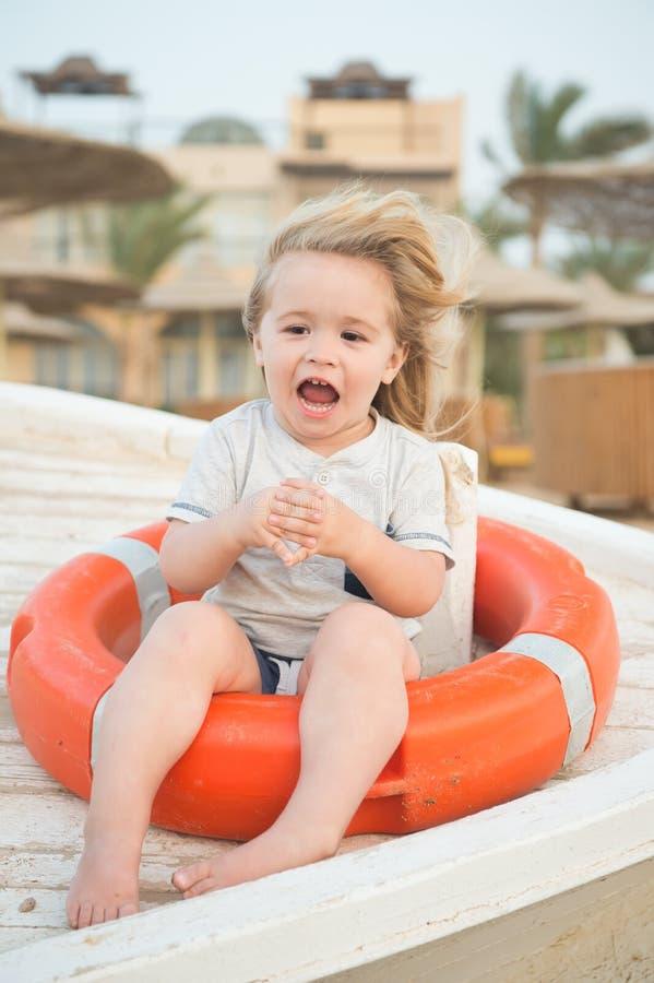 Säkerhet, räddningsaktion och hjälpbegrepp Det lyckliga barnet sitter i cirkelboj på solig dag Pys med livboj på den tropiska str arkivfoto