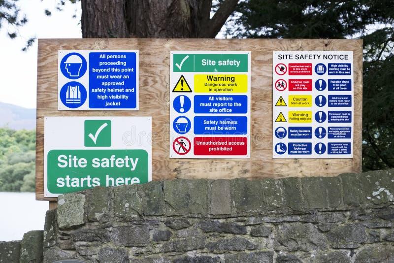 Säkerhet startar här och vård- tecken för meddelandet för säkerhetskonstruktionsbrädet var byggande arbeten äger rum arkivfoto