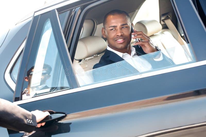 Säkerhetsöppningsdörr till den unga affärsmannen som sitter i den svarande påringningen för bil som ser att le för grabb som är f royaltyfri foto