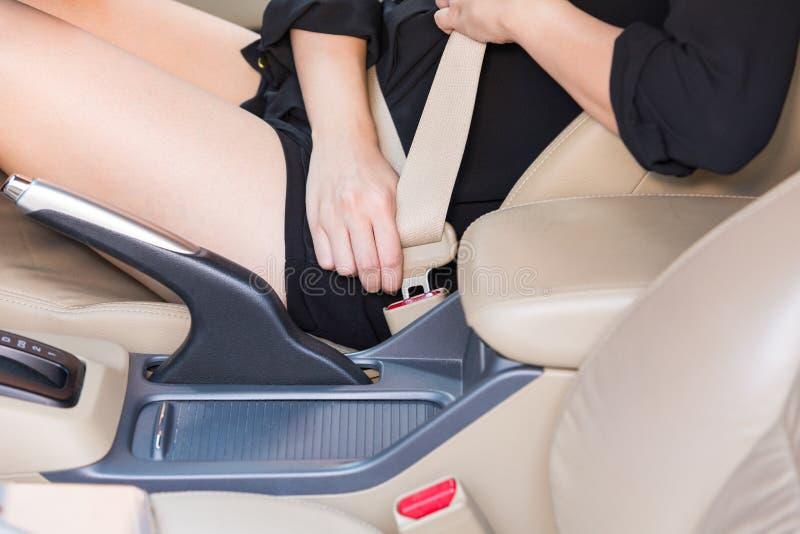 Säkerhetsbälte för kvinnahandfästande inom bilen arkivbild
