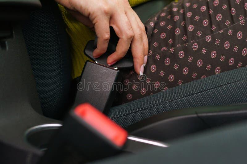 Säkerhetsbälte för säkerhet för kvinnafästandebil, medan sitta inom av veh royaltyfri foto