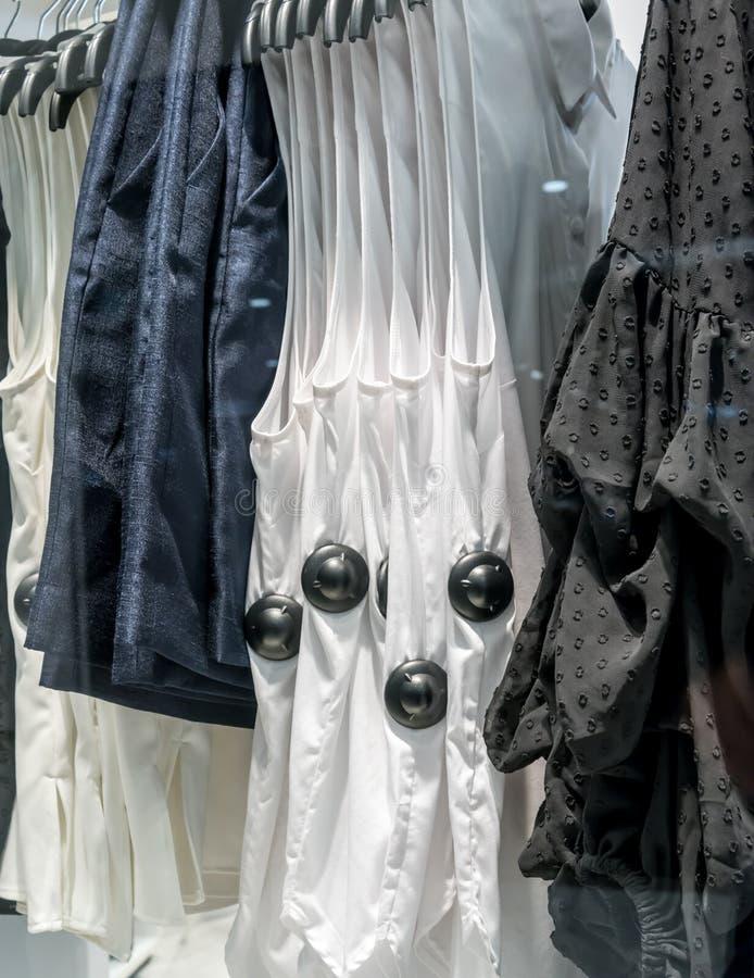 Säkerhetsetiketter eller avkännare på kläder i shoppinglager royaltyfri foto