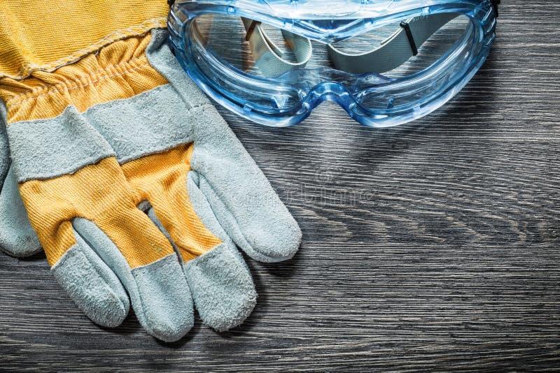Säkerhetsexponeringsglas för skyddande handskar på träbräde royaltyfri foto