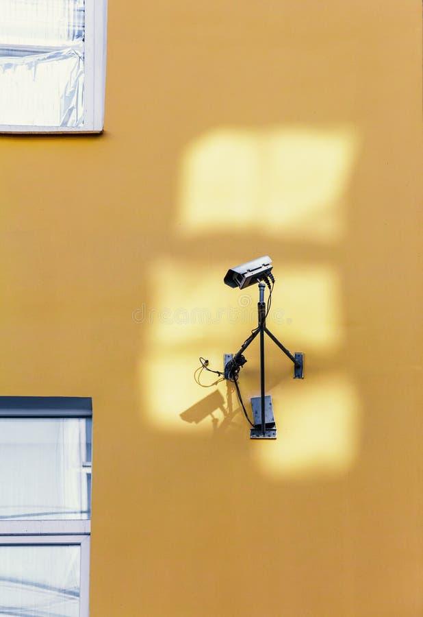 Säkerhetskamera på den gula väggen arkivfoto