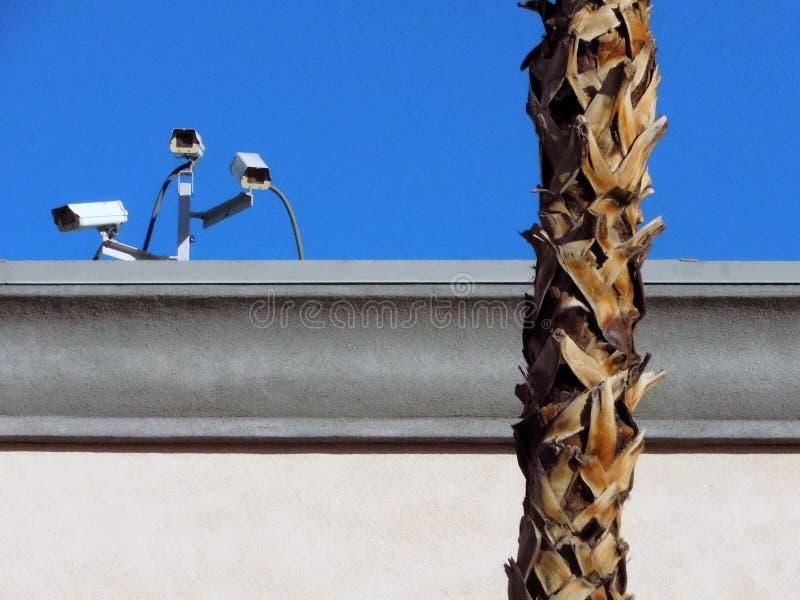 Säkerhetskameror uppe på ett lager som stirrar på parkeringsplatsen arkivfoto