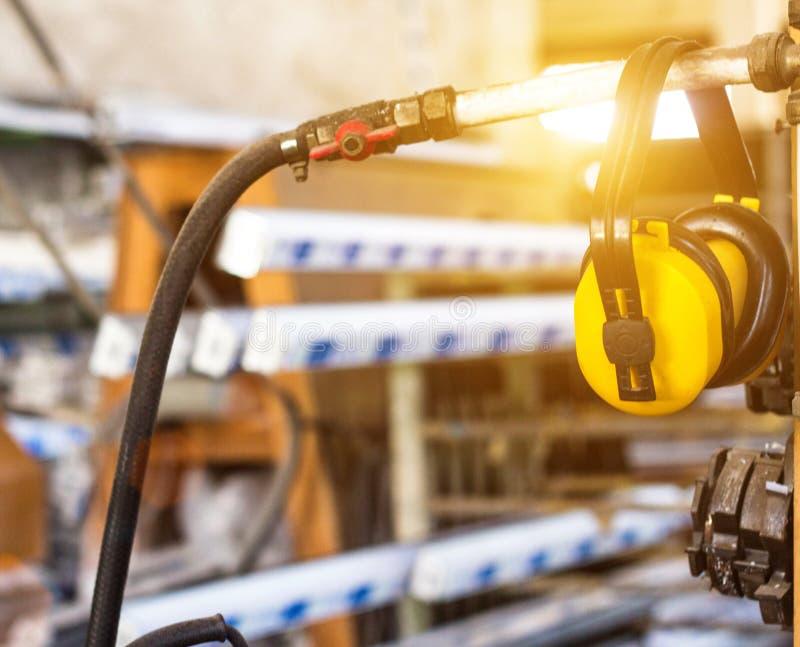 Säkerhetsoväsen på arbetsplatsen, gul hörlurar mot oväsenhängning i seminariet för tillverkningen av PVC-fönster arkivbilder