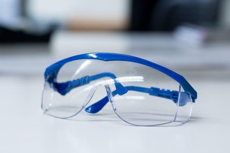 Säkerhetsskyddsglasögon och blåa handskar arkivfoton