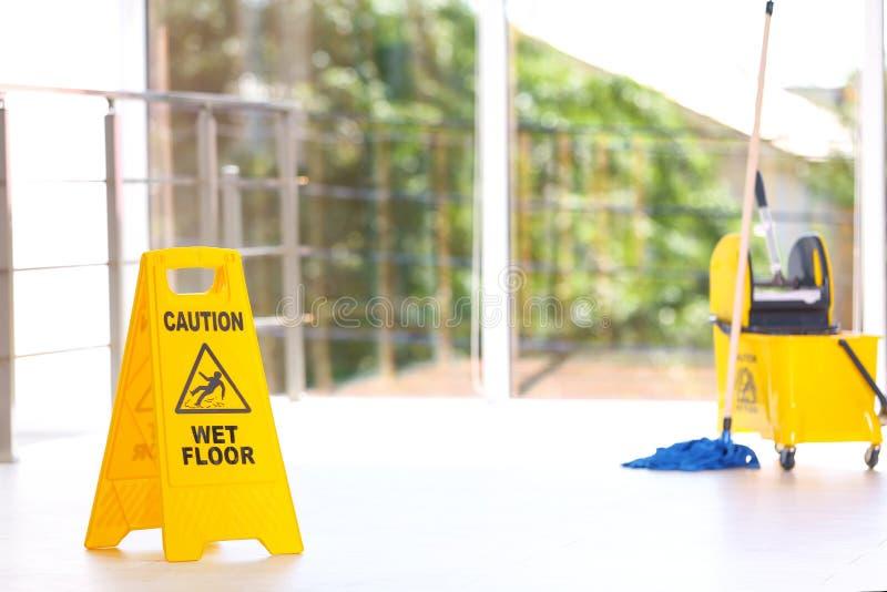 Säkerhetstecken med hinken för golvmopp för golv för uttrycksvarning den våta, inomhus rengörande service royaltyfria foton
