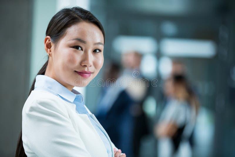 Säkert affärskvinnaanseende med hennes korsade armar arkivfoton