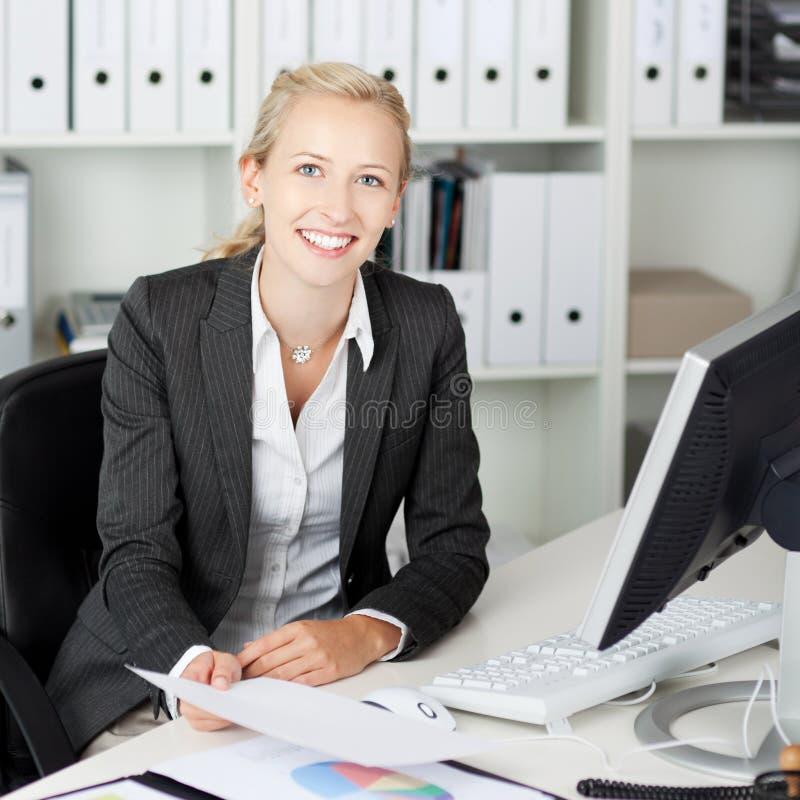 Säkert affärskvinnaHolding Paper At skrivbord arkivfoton