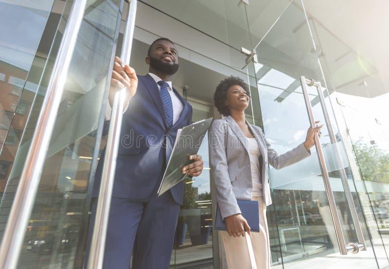 Säkert afrikanskt affärsfolk som går ut ur modern kontorsmitt arkivfoto