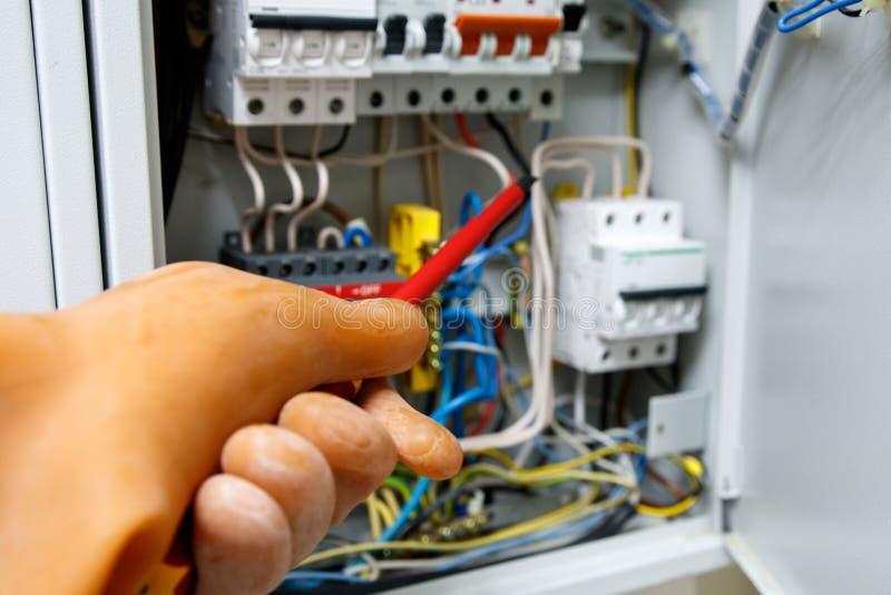 Säkert arbete med elektricitet som bär på handen av den dielectric gummihandsken arkivfoton