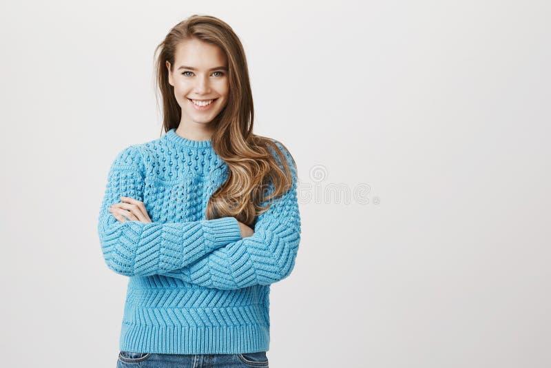 Säkert attraktivt europeiskt kvinnaanseende med korsade händer som i huvudsak ler och kastar en blick på kameran som uttrycker arkivbild