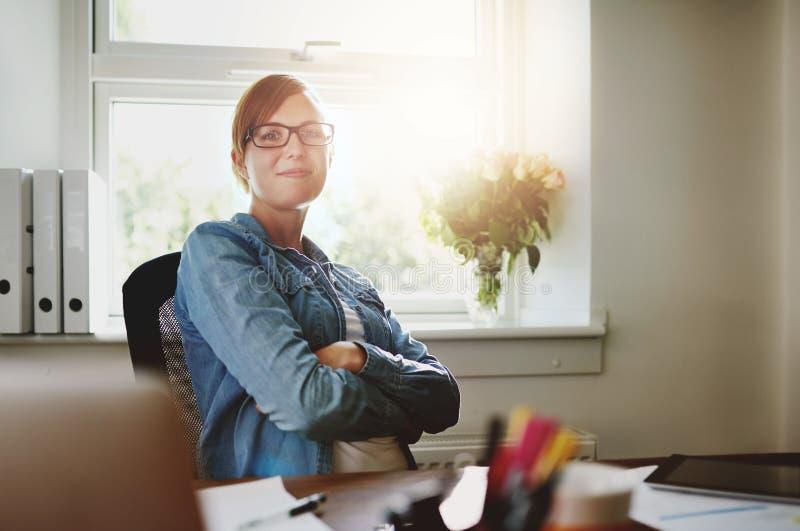 Säkert kontorskvinnasammanträde på hennes skrivbord royaltyfri fotografi