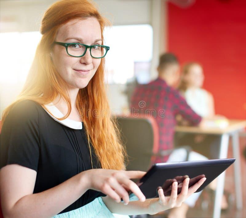 Säkert kvinnligt märkes- arbete på en digital minnestavla i rött idérikt kontorsutrymme royaltyfri fotografi
