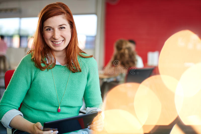 Säkert kvinnligt märkes- arbete på en digital minnestavla i rött idérikt kontorsutrymme arkivbilder