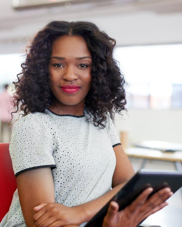Säkert kvinnligt märkes- arbete på en digital minnestavla i rött idérikt kontorsutrymme arkivfoton