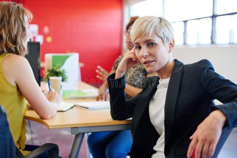Säkert kvinnligt märkes- sammanträde på hennes skrivbord för en idékläckning i rött idérikt kontorsutrymme arkivfoton
